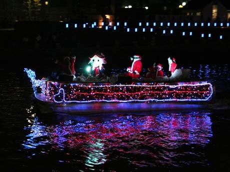 LED電飾で飾られた船に乗込むサンタたち