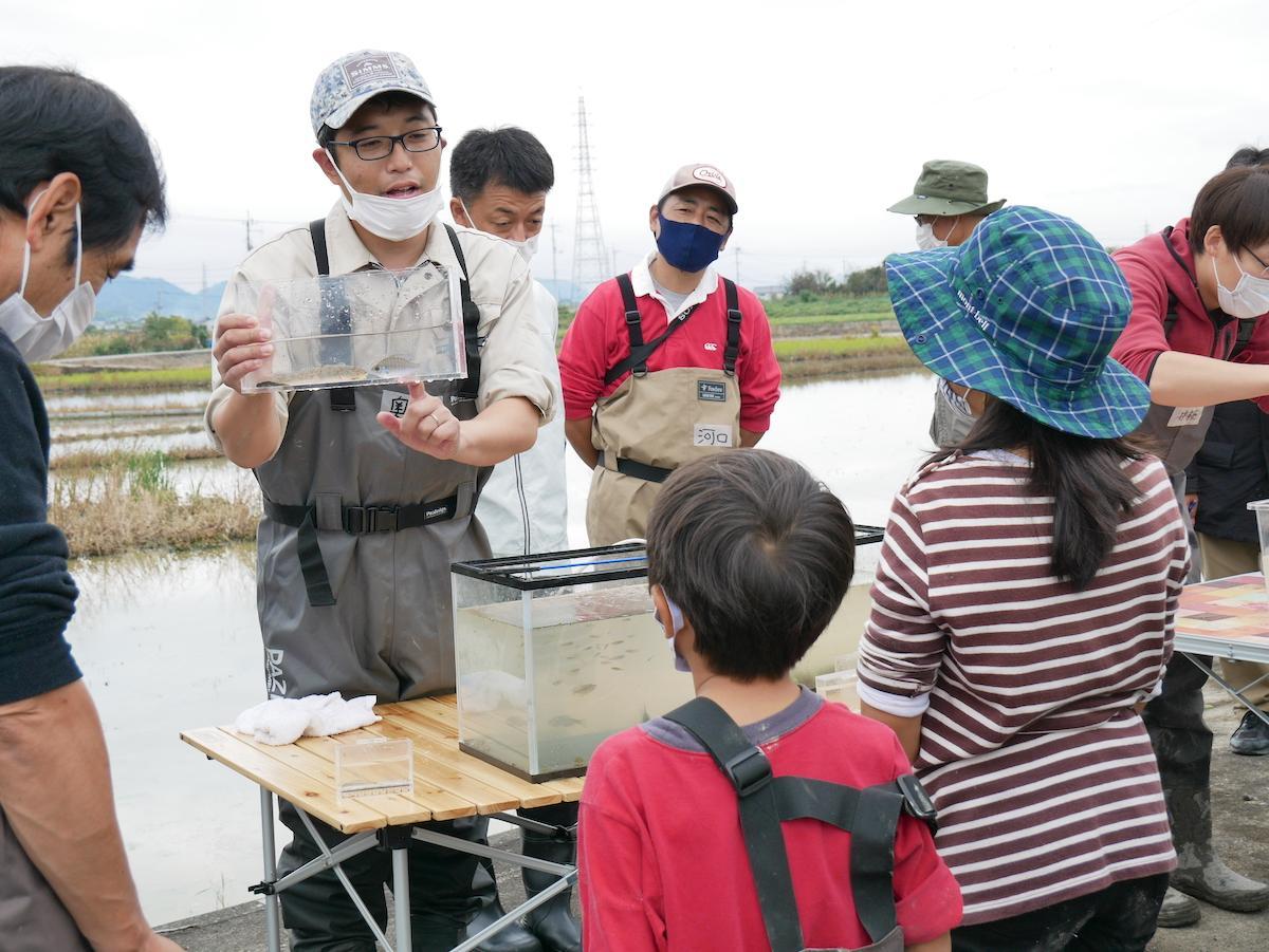 ボランティアチームで採取した淡水の生き物の説明を聞くメンバー
