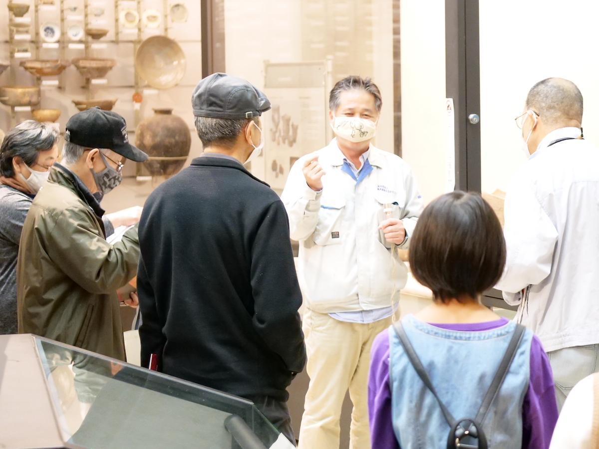 国内最古級の「論語木簡」の前で展示解説を聞く参加者