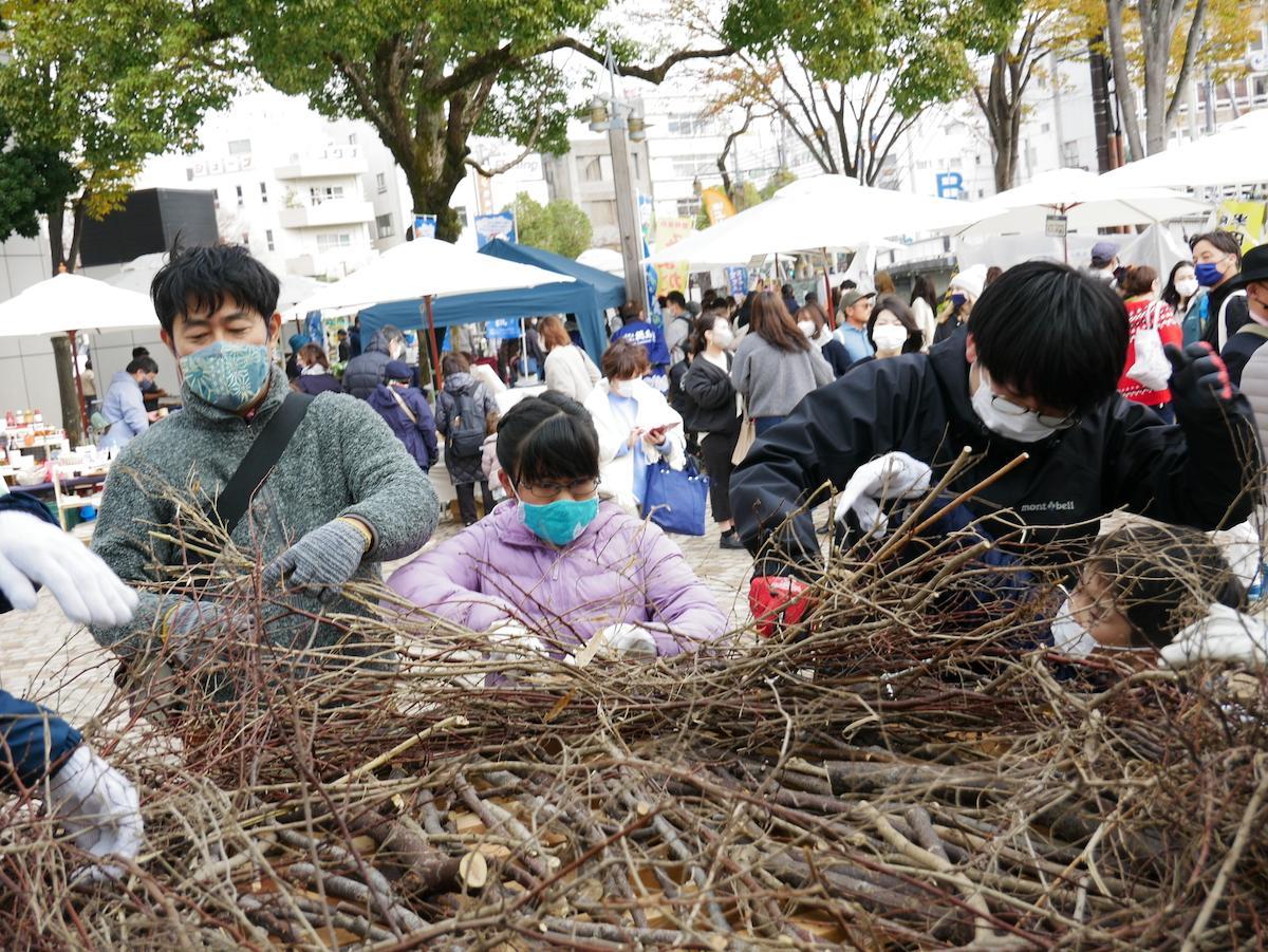 とくしまマルシェでコウノトリの巣作りに取り組む参加者親子