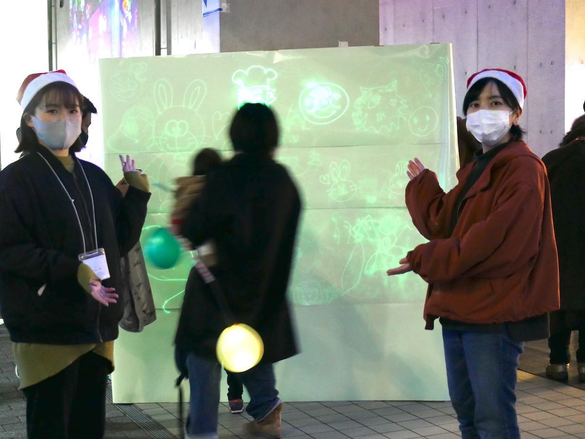 参加者が絵を描いた蓄光シートの前で四国大学生活科学の露口優波さん(右)と若松真由さん(左)