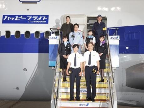 航空機機内から登場する矢口監督(最後列左)と出演者