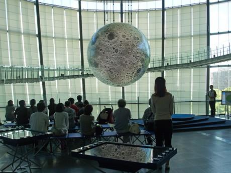 月に変身した地球ディスプレー「ジオ・コスモス」を前に、科学コミュニケーターの解説に耳を傾ける来場者