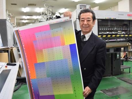 山田写真製版所で印刷されたばかりのカレンダーを手にする熊倉さん