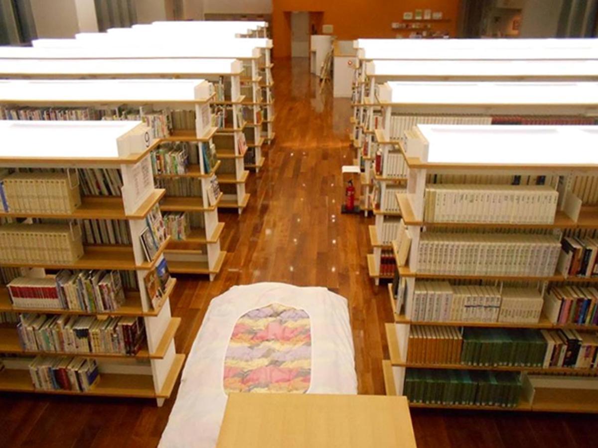 本に囲まれながら布団を敷いて就寝する