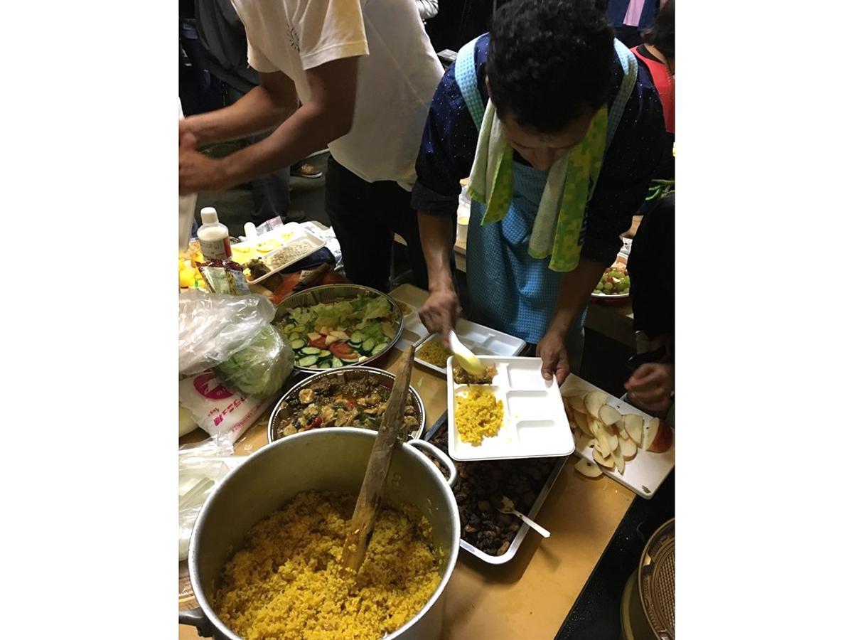 手作りのネパール料理を盛り付けるダルマ会長(右)
