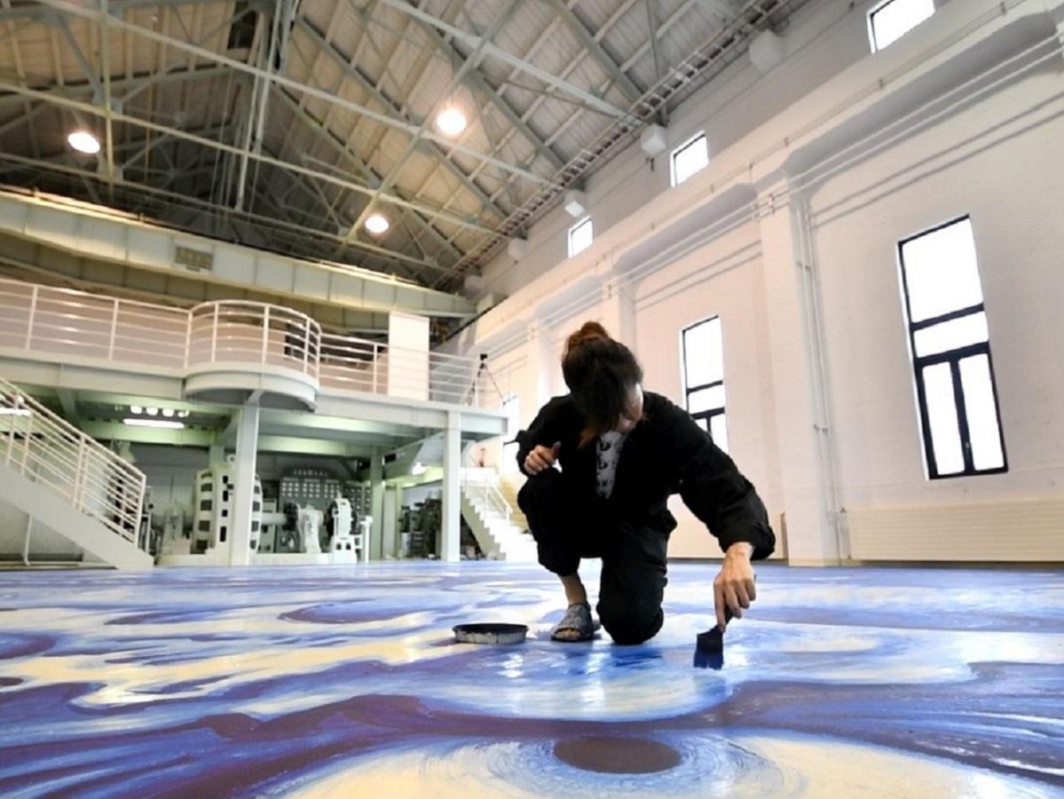 床に巨大生物を描く平井千香子さん