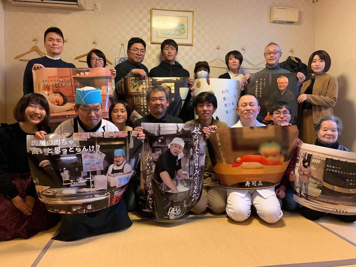 「寿司正」の山下稔さん(右)に完成したポスターを手渡す、森豪大さん