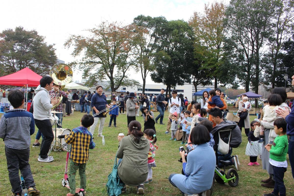 ブラスバンドの演奏を楽しむ親子などイベント来場者の様子