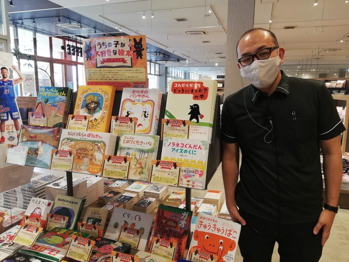 TSUTAYA LALAガーデンつくば店店長小松崎さんと「うちの子が大好きな絵本」フェアの様子