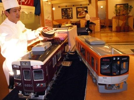 運行標識板ケーキを運ぶミニチュアの阪急電車と阪神電車