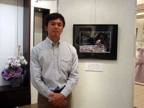 ツバルの現状を撮影した気象予報士の正木明さん。深刻化するゴミ問題を捉えた写真の前で。