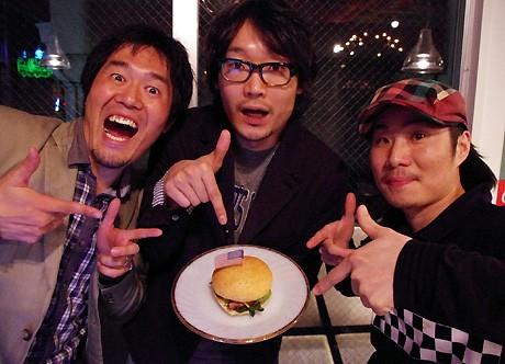 左から西日本ハンバーガー協会会長の薮伸太郎さん、コンテストで優勝したFM OSAKAのDJ・遠藤淳さん、寺川裕之店長