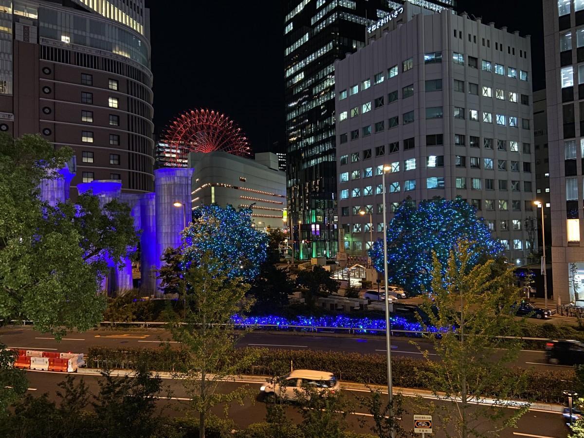 青色の光で彩られた街路樹と梅田吸気塔
