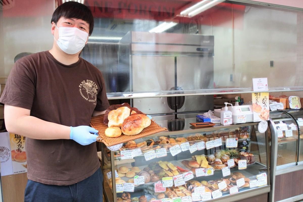 「塩フォカッチャ」など人気のパンを持つ売店責任者の西出聖さん