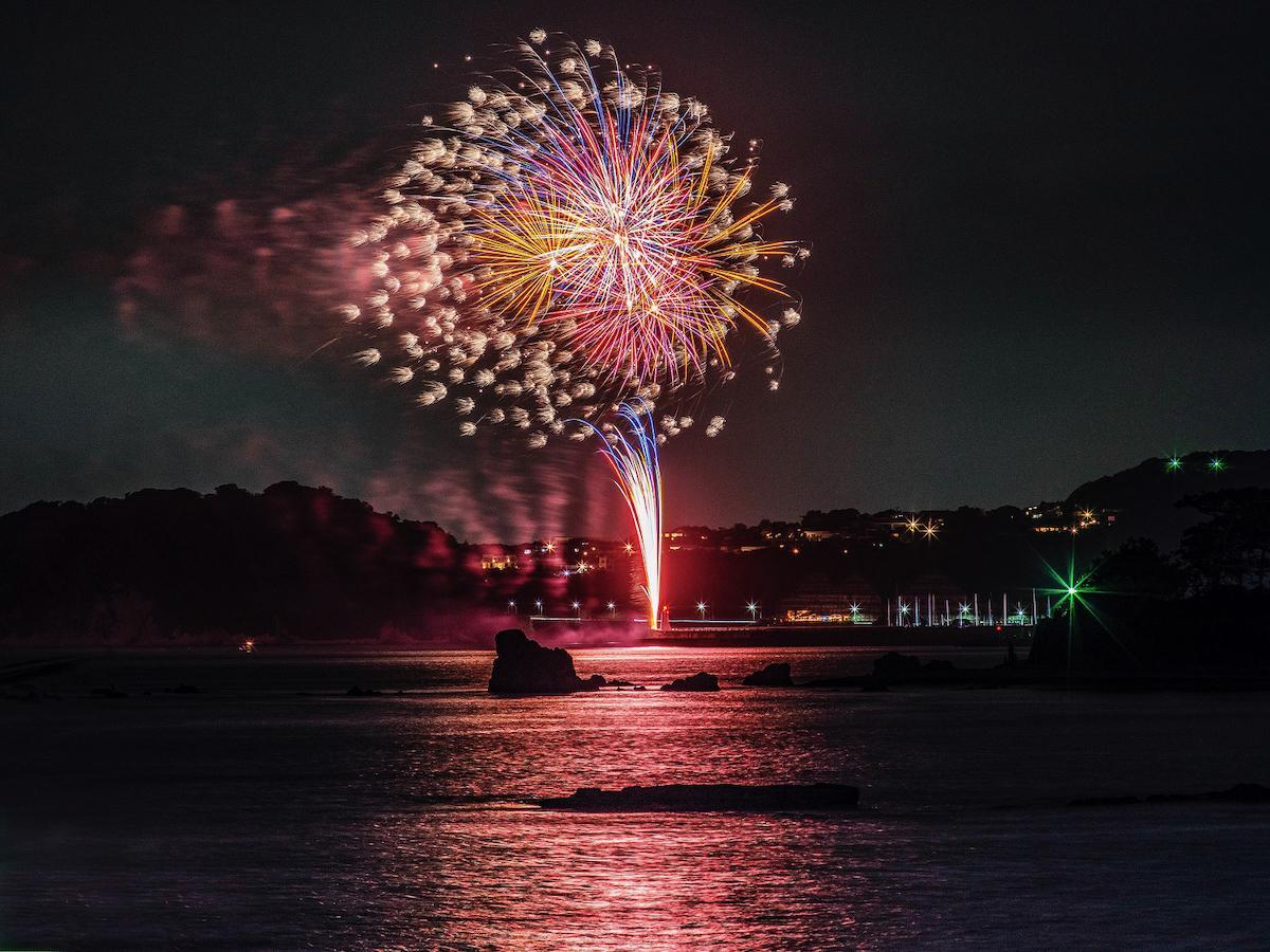 葉山港防波堤から上がった花火。背景は鎌倉(撮影:森崎清光)