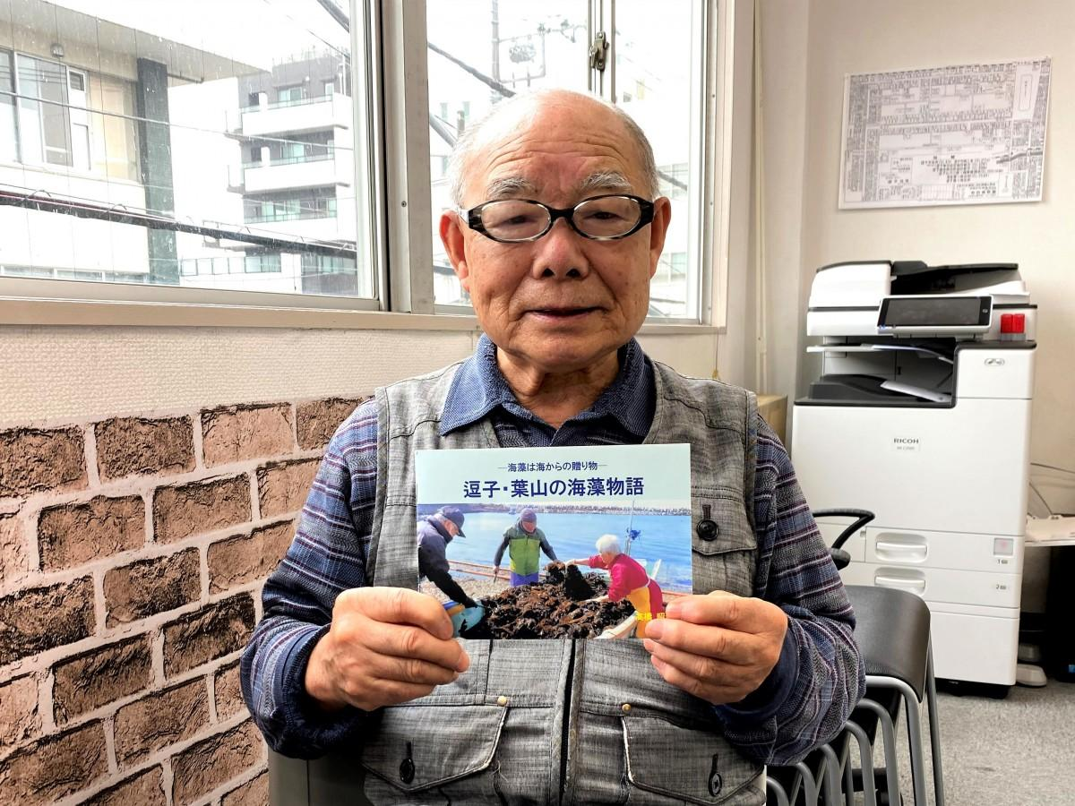 冊子「逗子・葉山の海藻物語」を手にする逗子在住の高橋昭善さん