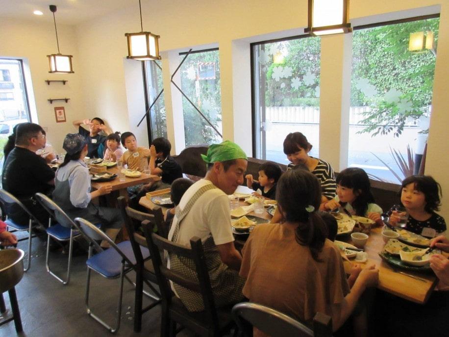 「子ども食堂」で食事を楽しむ親子とスタッフ