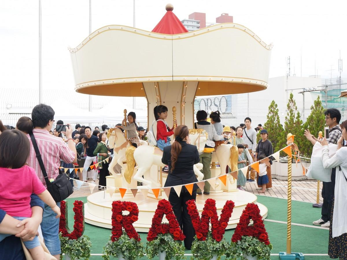 木製メリーゴーラウンドを楽しむ子どもたち=伊勢丹浦和店に「屋上遊園地」