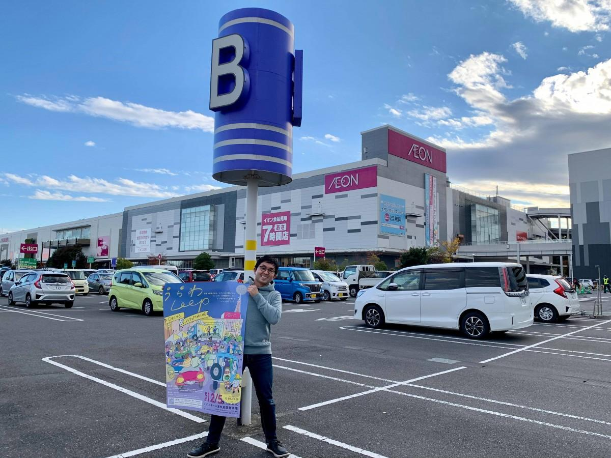会場のイオンモール浦和美園駐車場でポスターを掲げる、うらわClip代表の三ツ口拓也さん