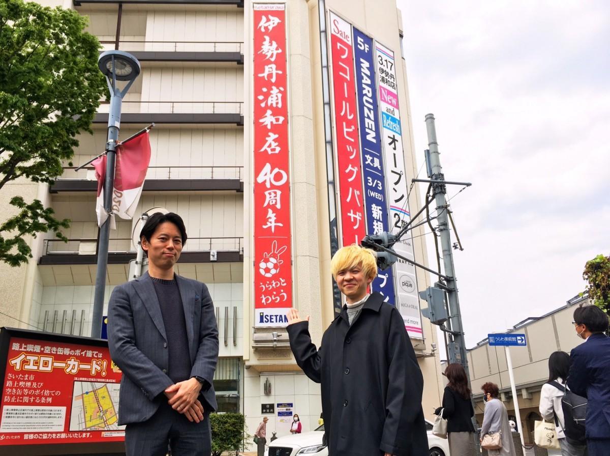 懸垂幕と立つ岩船ひろきさんと伊勢丹浦和店の甲斐正邦さん