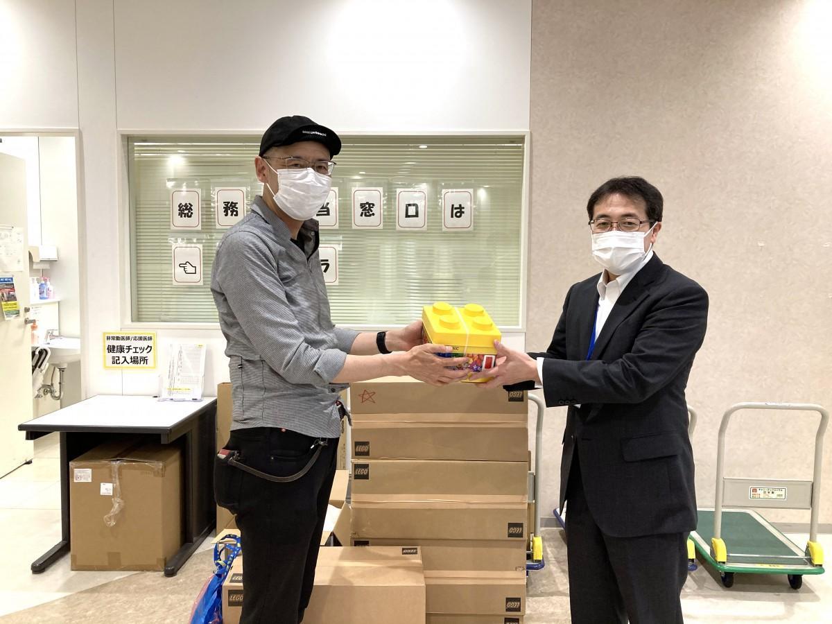 おもちゃカフェ「ブロックはかせ.LABO」の前原さんから埼玉県立小児医療センター事務局長へブロック玩具が手渡された