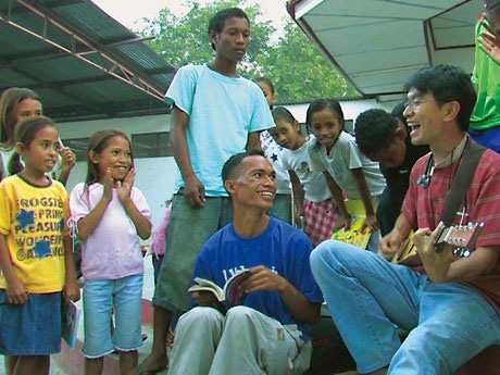 東ティモールの避難民キャンプで子どもたちと一緒に歌を歌う桑山紀彦さん。