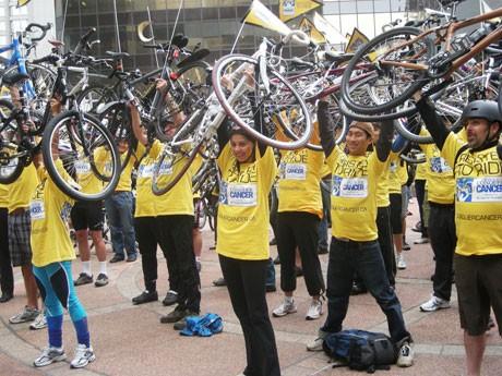 自転車を持ち上げて通行人に参加協力を呼びかけるがん撲滅自転車イベント「Conquer Cancer」の参加予定者。