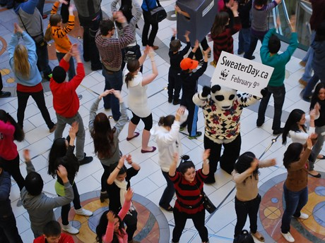 「National Sweater Day」(2月9日)参加を呼びかけて、メトロタウン・アトリウムでいきなり踊りだした100人以上のセーター集団