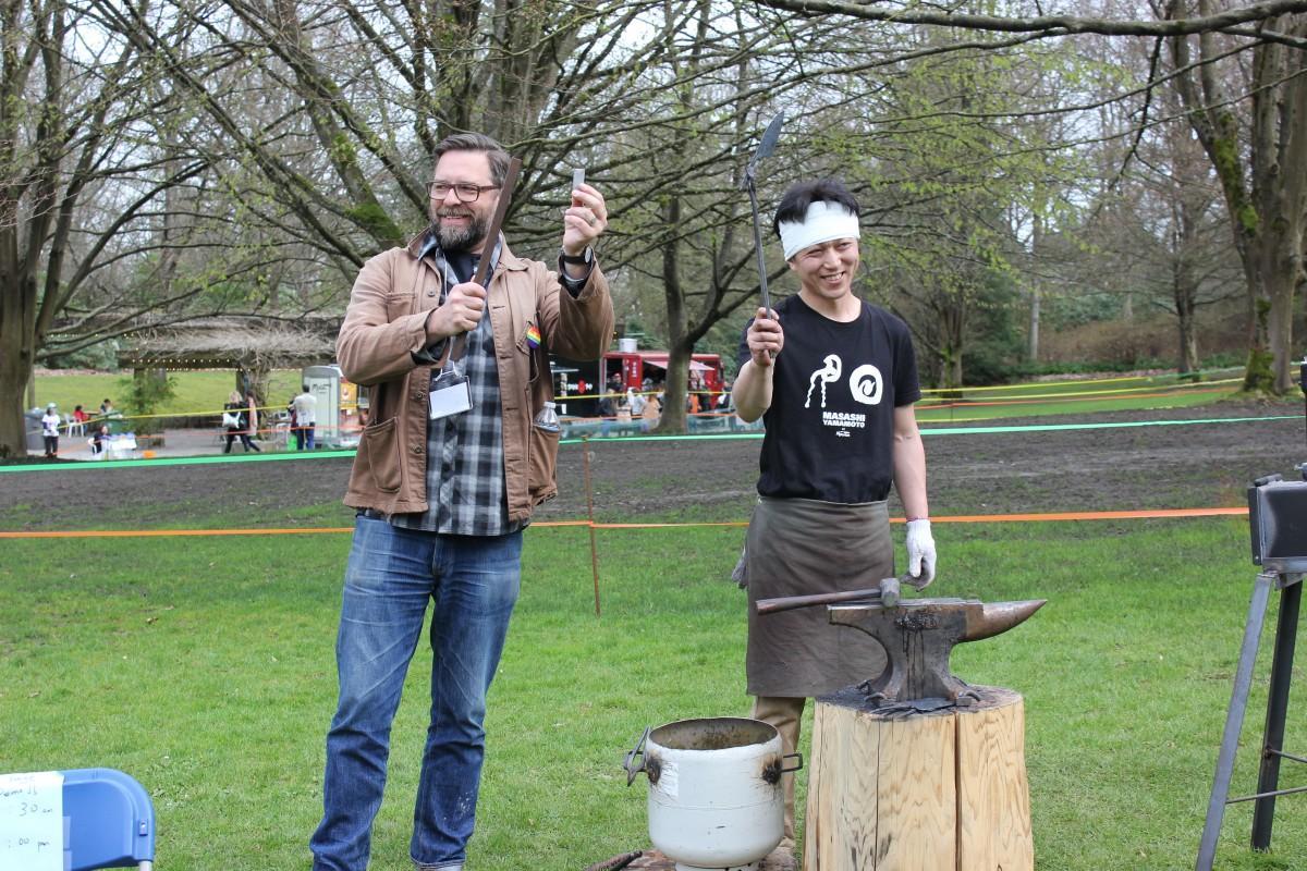包丁になる前の鉄片をかざすケビンさん(左)と包丁の形を成した刃物をかざす山本将史さん