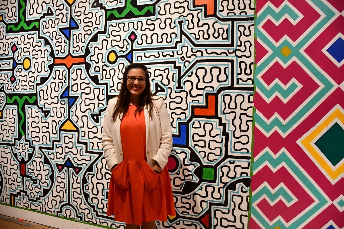 メキシコから招いた先住民族の女性が展示用に描いた壁画を前にするサナックス博士