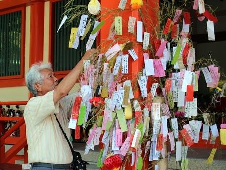 淡嶋神社で短冊をササにつける観光客