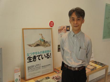 学芸員の奥村さんと、本展示のポスター