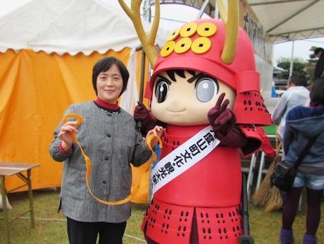 柿の皮むき大会で優勝した岩坪寿恵美さん(左)とゆっきー