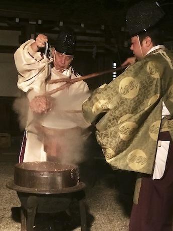 1835(天保6)年に寄進された釜で煮た小豆かゆから竹筒を取り出す様子