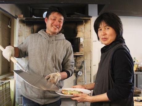 石窯で焼いたピザを取り出す代表の吉川誠人さん(左)と妻の幸子さん
