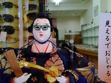 眼鏡店前に飾られた、眼鏡をかけた「お内裏様」