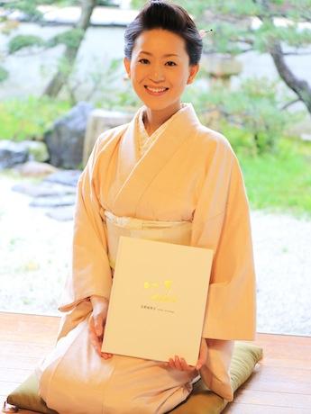 「一山」を手にほほ笑む、写真家の古賀絵里子さん