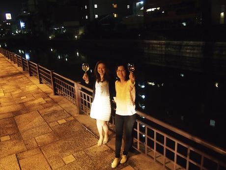 市堀川でグラスを掲げる齊尾茉里さん(左)