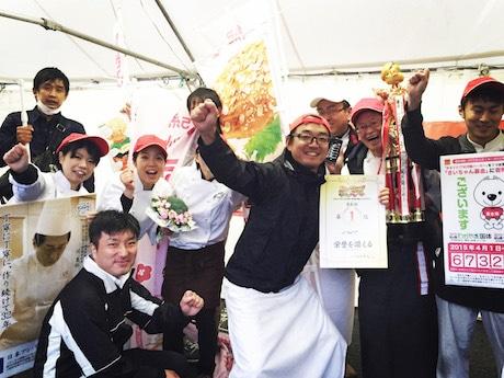 とっとりバーガーフェスタで2連覇を果たし賞状を手に喜ぶ今西さん(写真中央)