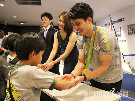 訪れた子どもと握手する田中佑典選手