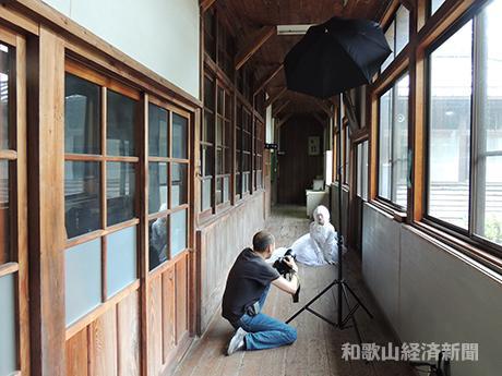 白藤小学校の校舎内で撮影する花谷さん(左)とコスプレイヤーのてらってぃーさん