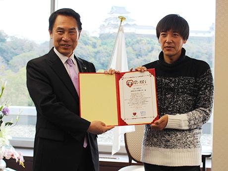 認定証を手にする尾花正啓市長(左)と波房克典日本ロマンチスト協会会長