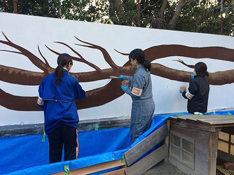 風が吹く方向に伸びる木をイメージして壁画を描く和歌山大学の学生たち