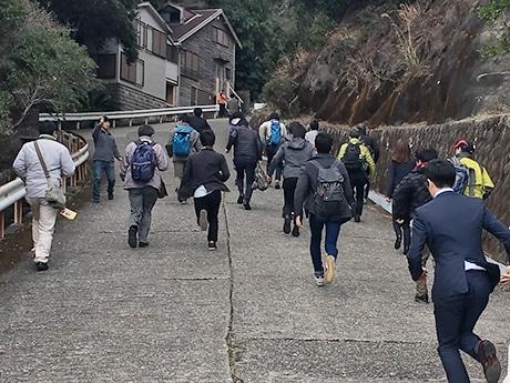 緊急停車した列車から高台目がけて避難訓練する参加者たち