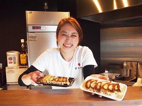 看板メニューの「元祖餃子」を手にした店主の大野由里子さん