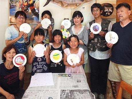 「紙皿絵本」のワークショップで完成させた作品を手にし笑顔を見せる参加者