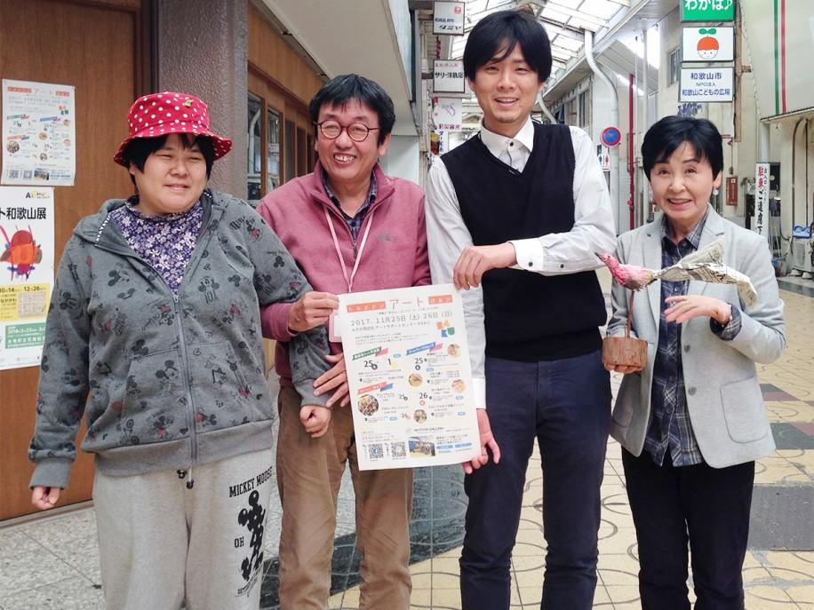 「アートサポートセンターRAKU」の前でメンバーと参加を呼び掛ける島久美子さん(右)