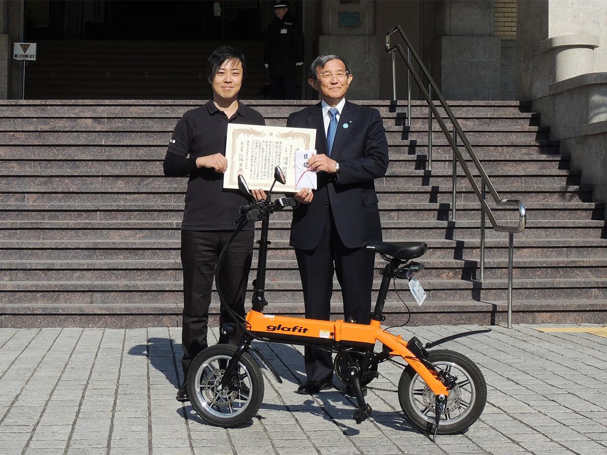 鳴海禎造社長(左)と仁坂県知事、寄贈されたみかんオレンジ色の「glafitバイク」