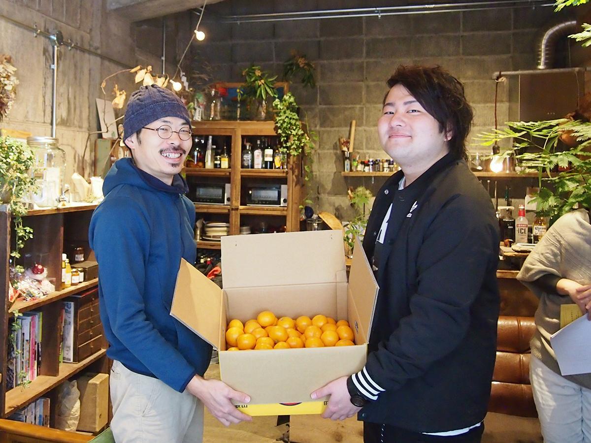 ミカンを受け取る「Guesthouse RICO」の宮原さん(左)と「幸美農園」の樫原さん